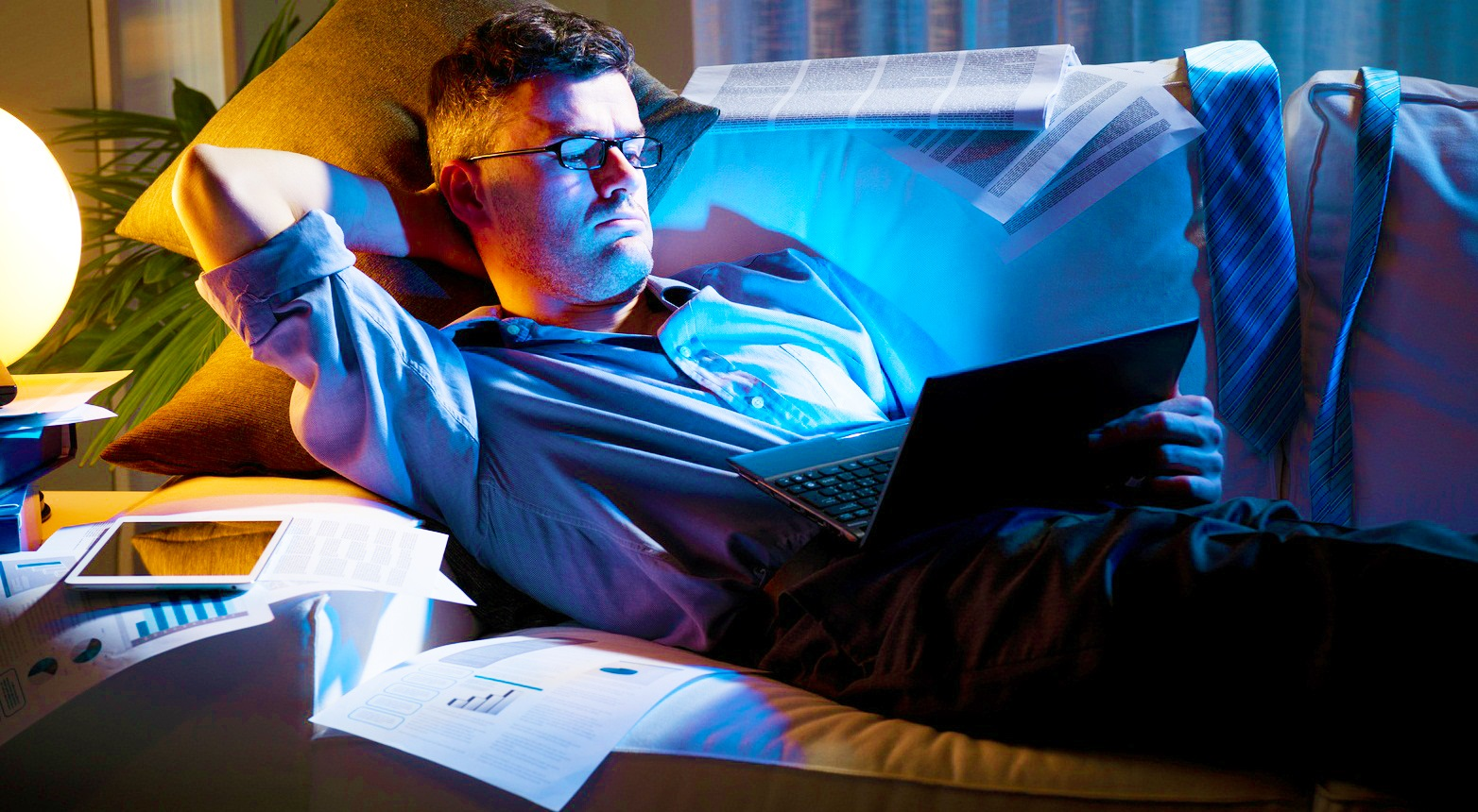 Businessman lying down on sofa and working with laptop late at night.