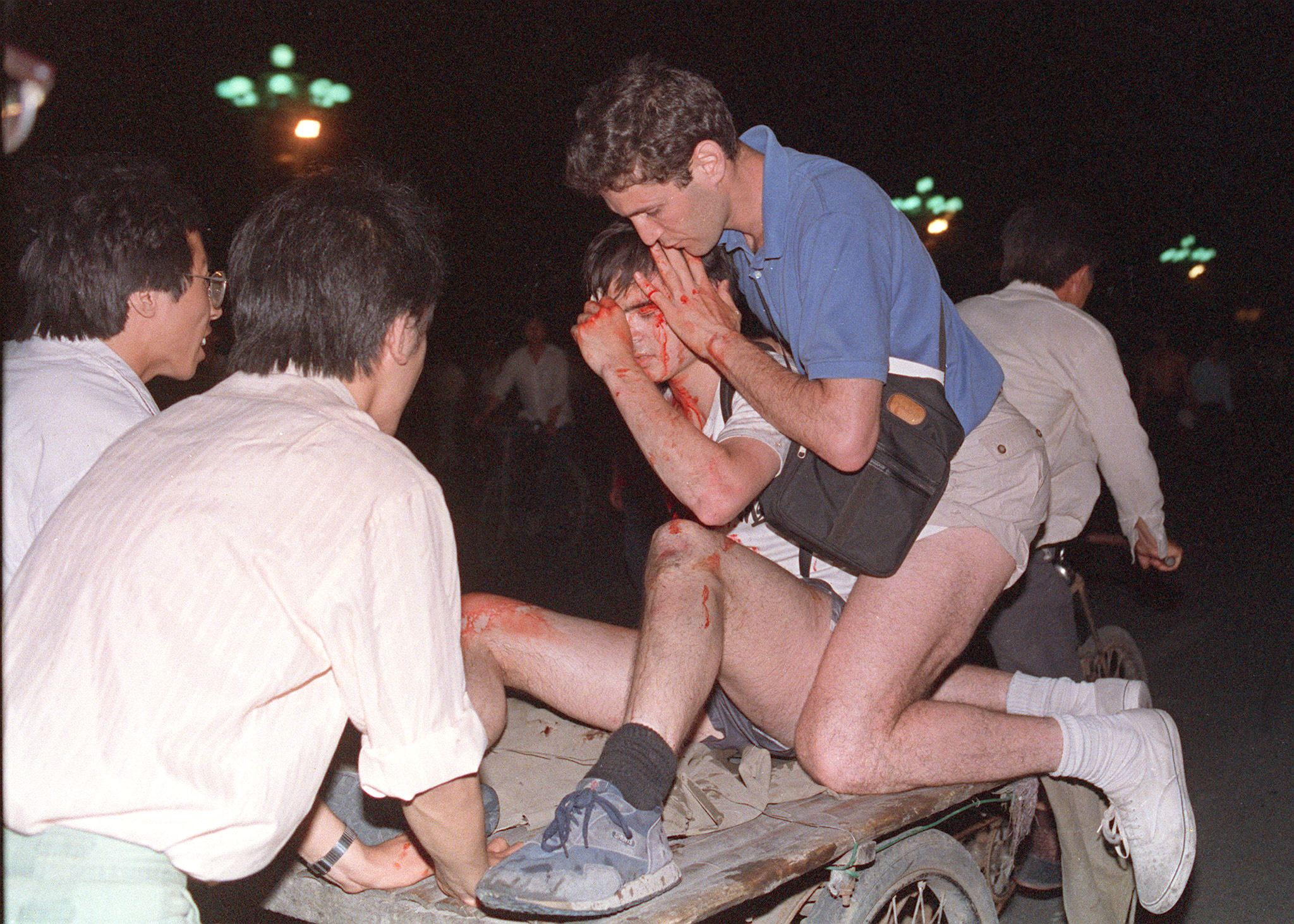 "(FILES) Taken care by others, an unidentified foreign journalist (2nd-r) is carried out from the clash site between the army and students 04 June 1989 near Tiananmen Square. On the night of 03 and 04 June 1989, Tiananmen Square sheltered the last pro-democracy supporters. In a show of force, China leaders vented their fury and frustration on student dissidents and their pro-democracy supporters. Several hundred people have been killed and thousands wounded when soldiers moved on Tiananmen Square during a violent military crackdown ending six weeks of student demonstrations, known as the Beijing Spring movement. According to Amnesty International, five years after the crushing of the Chinese pro-democracy movement, ""thousands"" of prisoners remained in jail. (Photo credit should read TOMMY CHENG/AFP/Getty Images)"